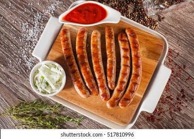 Sausages grilled on a wooden board with a white plate, spices and vokruk razmarin, fasfud concept - Shutterstock ID 517810996