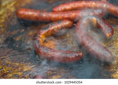 sausages grilling on a frying plate, extreme shallow focus