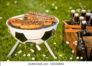 Sausages grilling on a soccer ball style BBQ alongside a wooden crate with bottles of craft beer in a spring meadow conceptual.