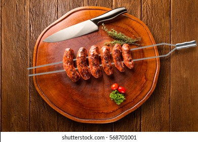 Sausages on the barbecue spit on wooden background