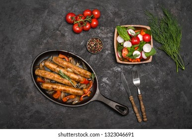 Sausages on the grill pan on the dark background. Top view. Frying pan with fried sausage, vegetables and fork and knife on a rustic wooden table.