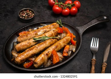 Sausages on the grill pan on dark background close-up. Side view. Frying pan with fried sausage, vegetables and fork and knife on a black wooden table.