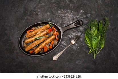 Sausages on the grill pan on the wooden background. Top view. Frying pan with fried sausage, vegetables and fork and knife on a rustic wooden table.