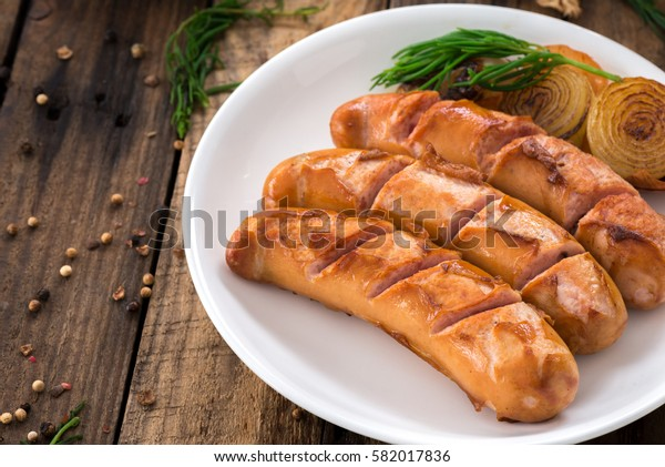 Sausages on the white plate and wood spoon fork on the wooden background. Top view