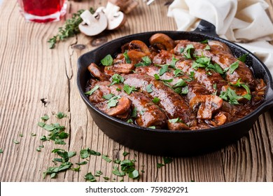 Sausages with onion and mushrooms gravy in cooking pan