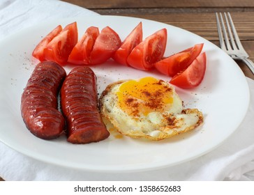 Sausages with tomato and egg on plate