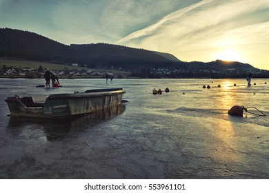 Saut du Doubs frozen lake during winter, Viller-le-Lac, France. Biggest natural ice skating in Europe. Sunset, people and boat blocked in ice,
