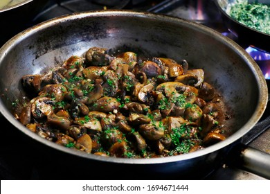 saute mushrooms and onions in a frying pan on fire
