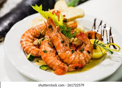 Saute shrimps with vegetables and lemon on white plate in the restaurant.