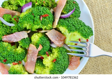Sauteed broccoli salad with bacon and garlic, ketogenic low-carb diet food top view macro