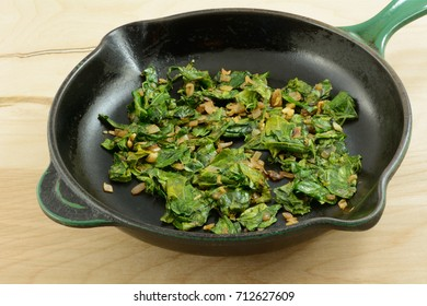Sauteed collard greens with chopped shallot in cast iron frying pan skillet