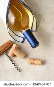 Sauvignon Blanc bottle wrapped in a towel on a gray tile surface with corks and antique corkscrew.