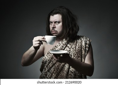 Savage man in skin of beast drink tea or coffee