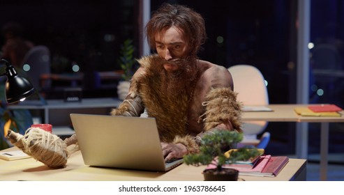 Savage office worker in prehistoric outfit sitting on office desk opening laptop getting scared starting interacting with modern technology device. Nighttime. Humor concept,
