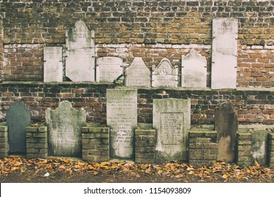 SAVANNA, GEORGIA / USA - MAY 22, 2018: Old tombstones on a wall at Colonial Park Cemetery in Savannah, Georgia.