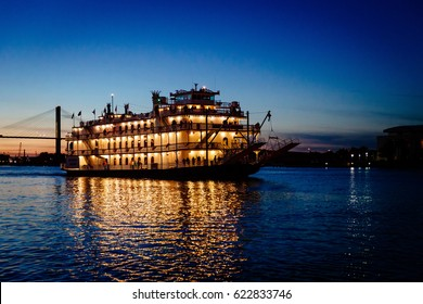 SAVANNAH, GEORGIA - 10 APRIL 2017: A riverboat cruises the Savannah River at sunset
