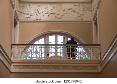SAVANNAH, GEORGIA - AUGUST 2, 2018: A photo of a balcony with historic sculptural relief design and unidentified security guard at Savannah's Telfair Museum.