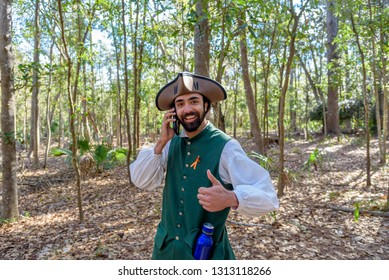 SAVANNAH GEORGIA, UNITED STATES - February 10, 2019: American Revolution Militia Historical Re-enactor Using a Cell phone and Giving a Thumbs Up Sign in Savannah Georgia at a Colonial Faire