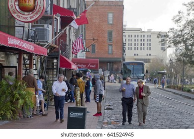 Savannah, Georgia, USA - January 20, 2017:  People exploring the Savannah Riverwalk, a popular destination with cobblestone streets, the Savannah River, restaurants, shops and art galleries