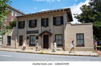 SAVANNAH, GEORGIA/U.S.A. - AUGUST 4, 2018: Photo of the First Girl Scout Headquarters in the U.S. and several unidentified women walking by it.  A plaque of founder Juliette Low is on the exterior.