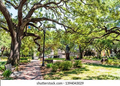 Savannah, USA - May 11, 2018: Reynolds park in Georgia during sunny day in summer with street and statue of John Wesley in center square