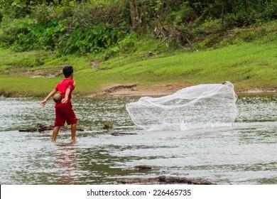 SAVANNAKHET,LAOS-OCTOBER 6 : The boy cast a net in the  river  at Savannakhet,Laos on October 6,2014.Cast a net is popular way to catch fish in Laos.