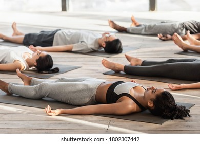 Savasana Pose. Diverse Yoga Class Members Meditating On Floor, Lying On Mats In Studio During Group Training, Free Space