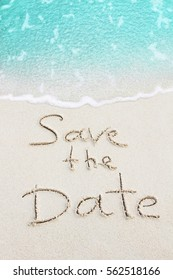Save The Date handwritten on sand, beach with ocean wave on background