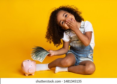 Save money concept. Cute little girl with piggy bank and banknotes on yellow background