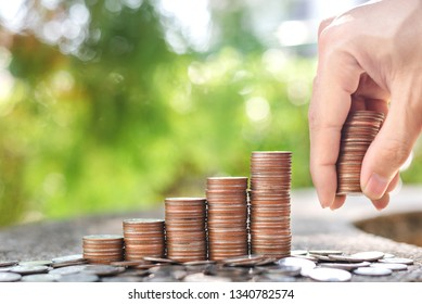 Save money concept with Hand holding coins and coin stack on blur background