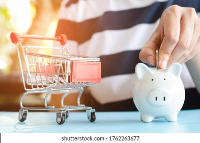 Save Money Concept.Woman Hand put coin to a piggy bank with shopping cart.Saving to shopping,eCommerce,marketplace.