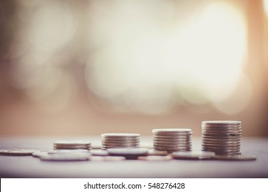 Save money and investment concept with coin stack growing graph with sunlight, selective focus