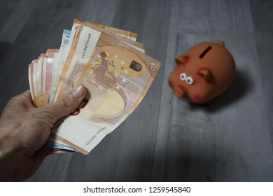 Save money in a piggy bank. Hand showing a wad of money to a piggy bank.