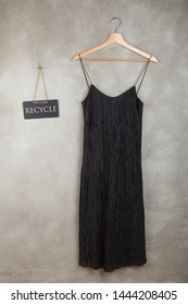 Save planet concept - blackboard with text Recycle and beautiful little black dress on a hanger on grey background