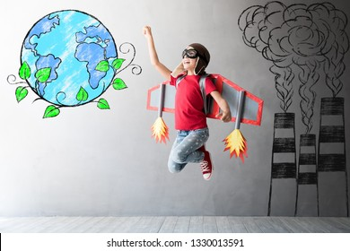 Save the planet. Happy child playing with toy jetpack. Kid pilot having fun at home. Earth day concept
