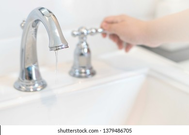 Save the water concept.Hand closing valve on sink in bathroom. Water dripping to stop running as hand turn off the faucet.Detect-a-Leak week.