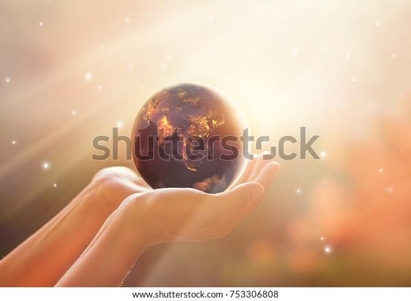 Rettet die weltweite Energiekampagne. Planet Erde auf menschlichen Händen zeigen Energieverbrauch der Menschheit in der Nacht, Elemente dieses Bildes von der NASA bereitgestellt.