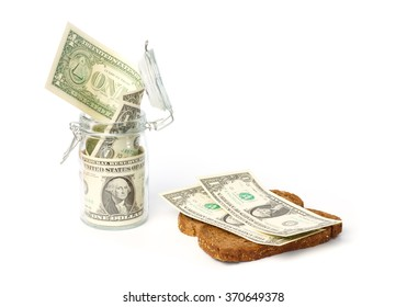 Saved dollars in a storage jar and on a slice of bread