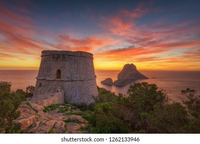 Savinar watchtower and Es Vedra Island at sunset with cloudy red sky , Ibiza .