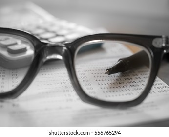 Saving Account Book from Bank for Business Finance with pen focused in eyeglasses lenses