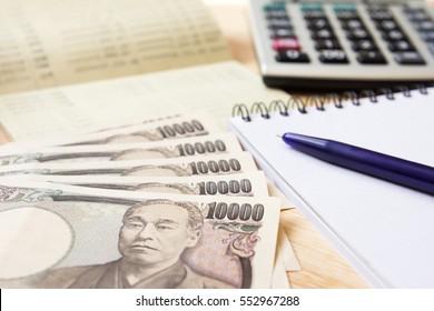 Saving account passbook, japanese yen, note book, calculator and pen