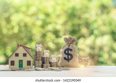 Saving for buying a house / first time home buyer concept : US dollar bags, residential house model, piggy bank on rows of rising coins, depicts saving for human basic needs and paying for living cost
