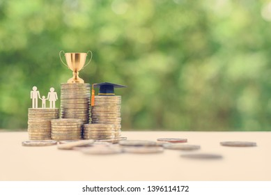 Saving for child education, financial concept : Golden trophy cup, black graduation cap, family members with a kid on rows of rising coins, depict money or asset arrangement for learning and knowledge