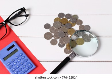 saving concept. coin on wooden table with calculator and glasses