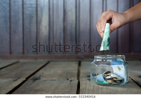 Saving concept Image Of Kid Hand Putting A Coin Into Glass Bottle.