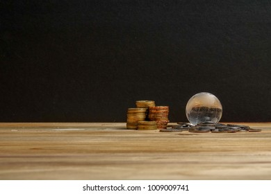 SAVING CONCEPT. Stack of coins on the wooden table over black background.
