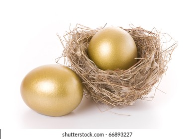 Saving concept - Two golden eggs and a nest isolated on white