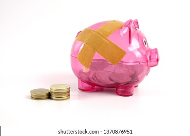 SAVING  DETERIORATE CONCEPT. Red piggy bank with bandage and small stack of coins.