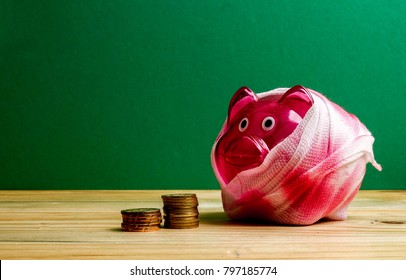 SAVING  DETERIORATE CONCEPT. Red piggy bank with bandage and small stack of coins on the wooden table over green background.