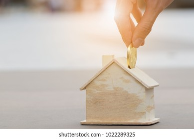 Saving for a dream house. Close up of a man hand putting coin into a mock up wooden house.